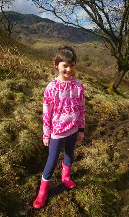 Image of dark haired girl wearing pink top and wellies with dark leggings among bare trees in hills