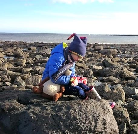 Image of girl in blue coat, hat and wellies holding teddy and writing while sitting on large rock on rocky coastline with sea behind