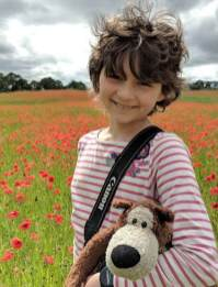 Image of girl with short curly dark hair wearing pink and white stripe top carrying brown teddy bear with poppy field behind