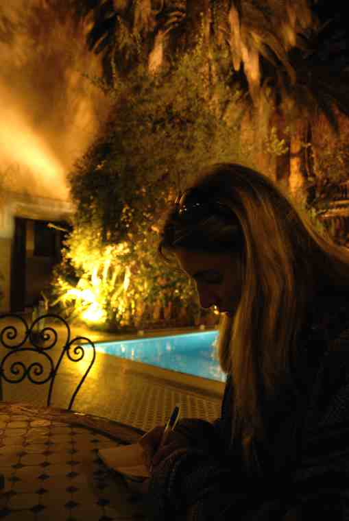 Image of long haired woman in silhouette writing at a table in a riad garden with pool behind in semi-darkness and palm trees