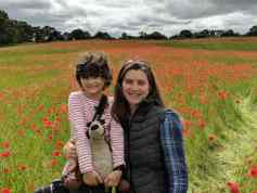 Image of woman in navy clothing with dark hair and sunglasses with child in striped top holding teddy in field of poppies