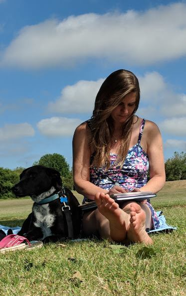Image of woman with long brown hair in floral blue dress sitting on grass writing with black dog next to her