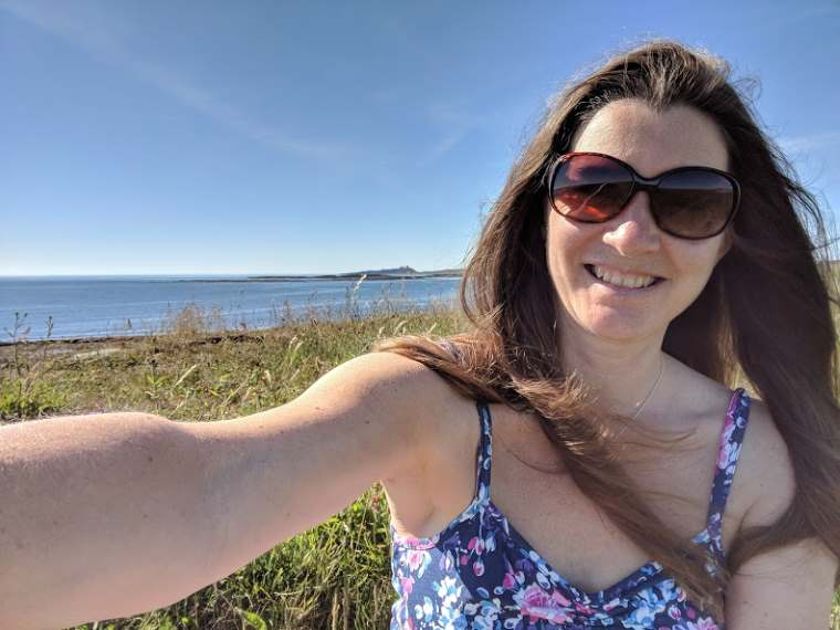 Image of woman with long dark hair, floral blue dress and sunglasses taking selfie with seascape in background