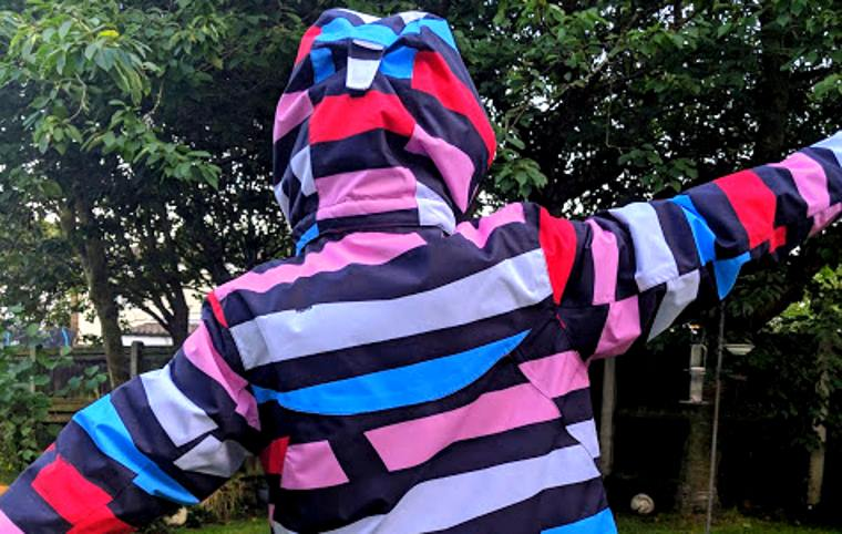Image of back of red, black, blue and white winter kids ski jacket with hood