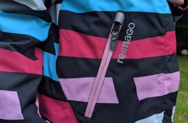 Image close up of pink external pocket zip on pink, white, black and blue waterproof winter kids coat