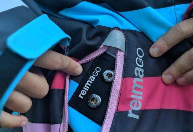 Image close up of pocket on pink, black, blue and white winter ski jacket showing two circular connectors