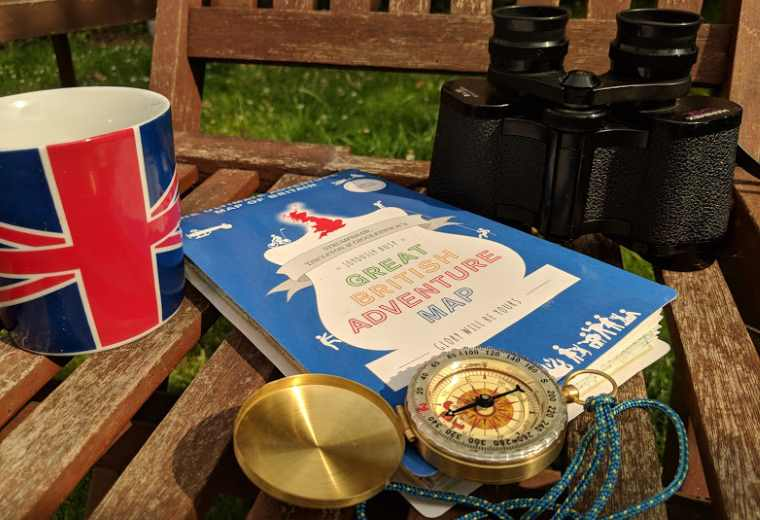 Image of blue coloured map on wooden garden chair with brass compass, binoculars and union flag mug
