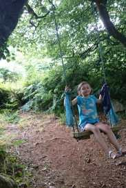 Image of girl in blue T-shirt and shorts sitting on wooden swing under tree in woods