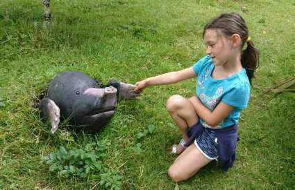 Image of girl in blue T-shirt and shorts with ponytail sitting in grass holding hands with a giant wooden mole peeping from the earth