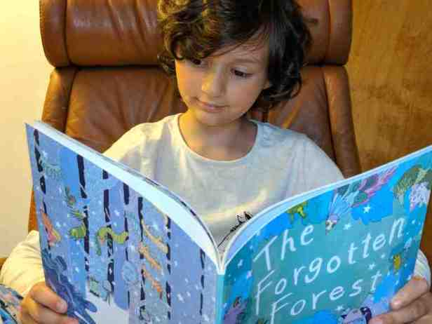 Image of girl with short brown hair and cream jumper reading a picture book titled The Forgotten Forest