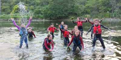 Image of group of children in wetsuits throwing weed and splashing in water at edge of river with bank behind