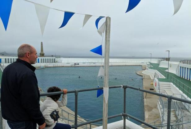 Image of man and child standing near white railings overlooking outdoor lido with sea in background and grey misty sky