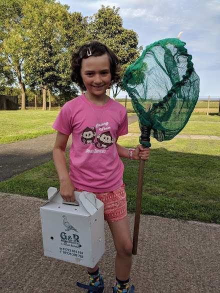 Image of smiling girl in pink top holing green net, and white cardboard bird carrier with fields behind