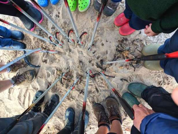 Image looking down on a circle of legs and feet in the sand wearing multicoloured boots with litter picking sticks inside the circle