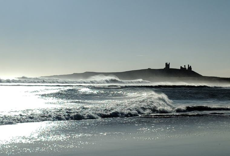 Image of castle ruin in background with sparkling beach and ocean in front with white horse waves