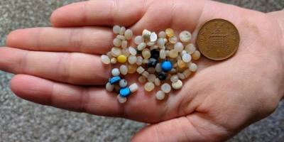 Image of child's hand holding out several tiny multicoloured plastic beads with 1 penny piece for size comparison