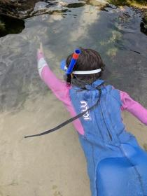 Image of dark haired child in blue and pink wetsuit and snorkel & mask snorkelling in shallow rockpool on beach