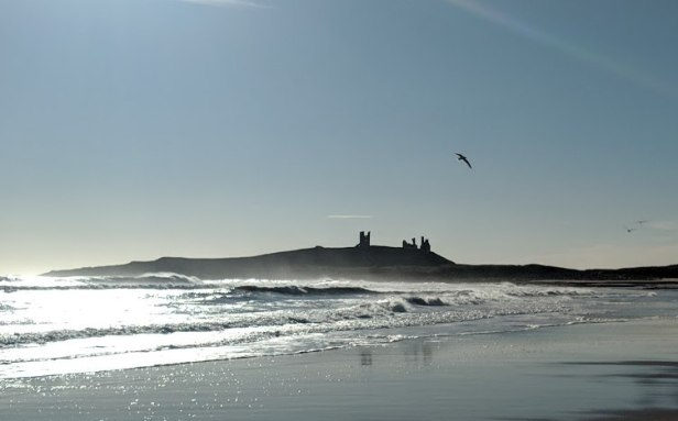 Image of distant ruined castle sihouetted with bright sky behind with sea, waves and beach in front