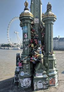 Image of old fashioned metal street light on stone plinth covered in graffiti and padlocks with river and white big wheel in background
