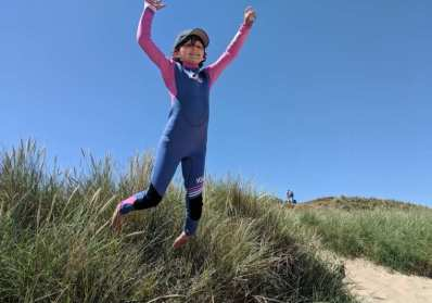 Image of smiling girl in blue and pink wetsuit with cap on jumping from grassy sand dunes