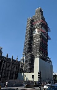 Image of tall clock tower completely covered in scaffolding with only clock face visible