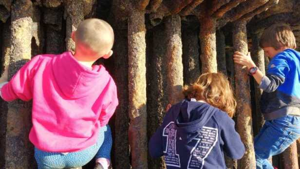 Image of three children climbing in rusted metal tube-like object