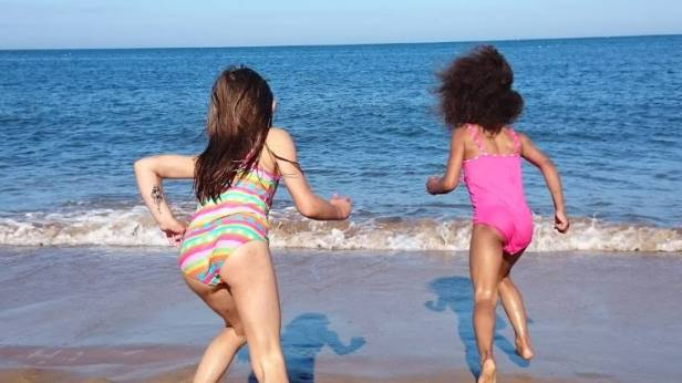 Image of two girls in swimsuits with back to camera running into the sea