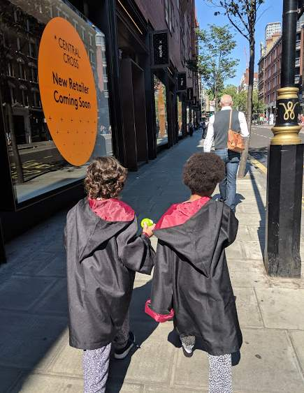 Image of two girls with backs to camera wearing black robes walking along city street