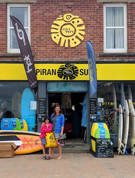 Image of woman and girl standing outside Piran Surf surf shop with surfboards outside