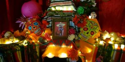 Image of Day of the Dead altar with coloured sugar skulls, candles, photos, brightly coloured blankets and orange marigold flowers