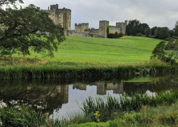 Image of castle in background reflected in still foreground river with fields and trees around