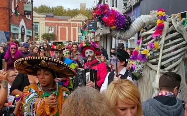 Image of crowd in street watching men in Day of the Dead costumes and giant skeleton puppet with flower headdress