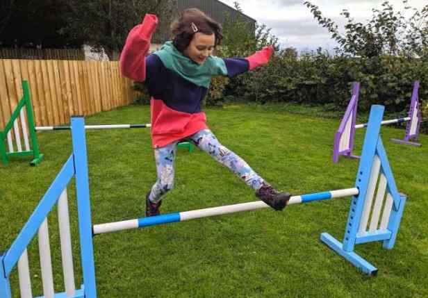 Image of dark haired smiling girl in red, green and blue clothing jumping over multicoloured dog agility bars with no dog