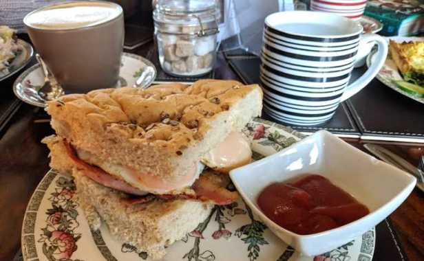 Image of egg and bacon in large triangular roll with ramekin of ketchup and striped mugs on table
