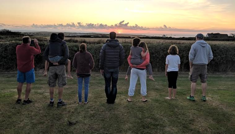 Image of family of 9 standing in a row on grass with backs to camera looking towards low sunset in sky