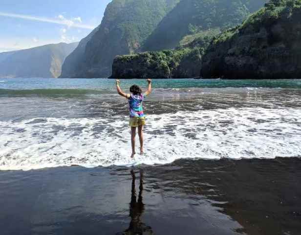 Image of girl in yellow shorts and bright top with back to camera jumping in surf on black sand beach with high cliffs and sea behind
