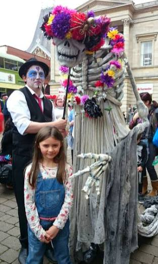 Image of girl wearing dungarees in street in front of giant Day of the Dead skeleton puppet wearing flower headdress being moved by man in black waistcoat