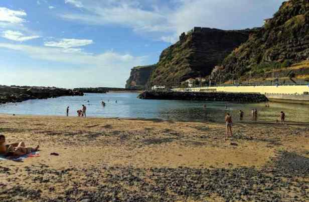 Image of golden sand and stony beach with rock-sheltered swimming area behind, cliffs behind