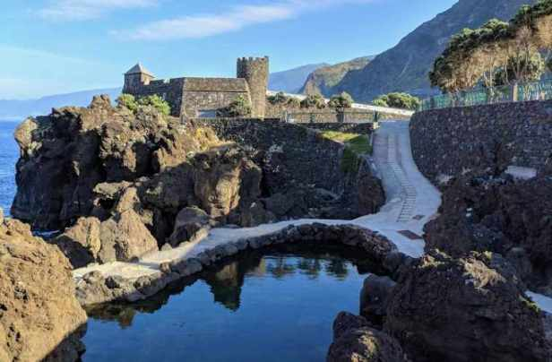 Image of natural sea pools edged with volcanic lava rock with castle, cliffs and sea in background