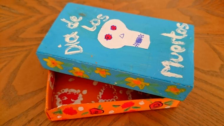 Image of orange and turquoise box painted with white skull and the words Dia de Los Muertos