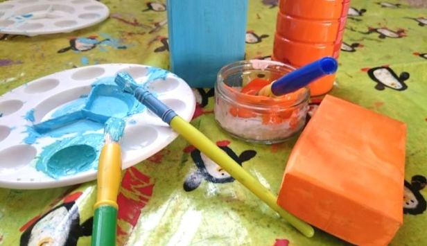 Image of painted matchbox and bottle of orange and bottle of blue paint with two white paint pallets with brushes
