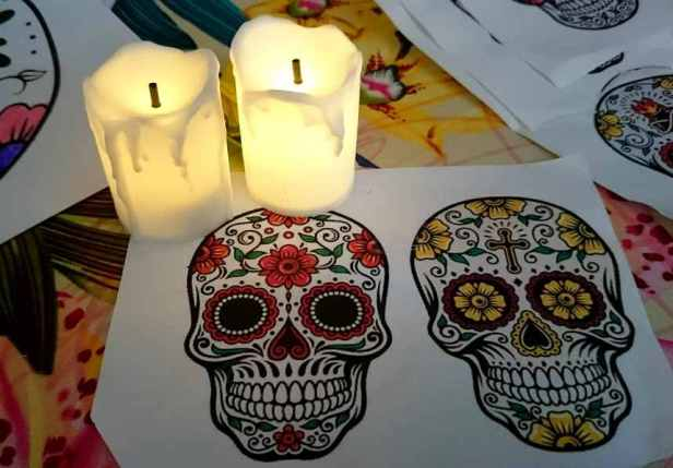 Image of two lit candles on craft table with picture of two coloured sugar skull face masks