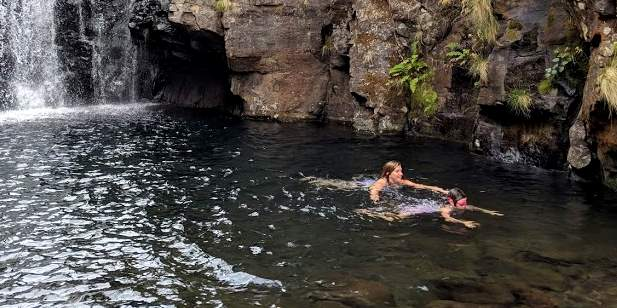 Image of two people swimming in large pool at bottom of waterfall surrounded by rocky cliffs