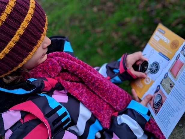 Image of child in red and yellow hat with coloured coat looking at leaflet and holding a silver metal compass