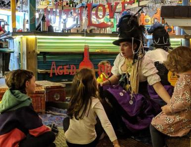 Image of children sitting on floor in front of mirror in Turtle Bay restaurant with storyteller dressed as a pirate