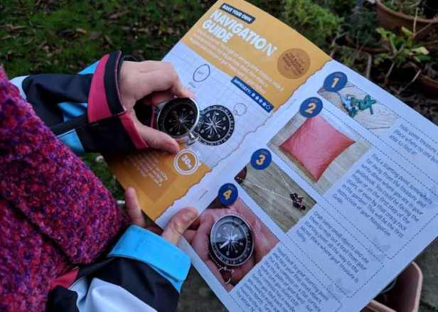 Image of close up child's hand holding silver metal compass over leaflet called Navigation Guide from a Mission Adventure Box