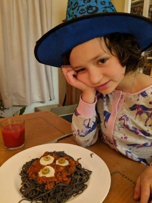 Image of girl in blue witches hat with plate of black spaghetti, bolognaise and eyeballs