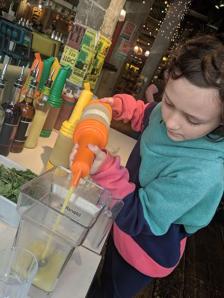 Image of girl pouring orange juice into cocktail glass