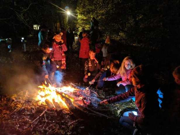 Image of group of children around a campfire in the dark