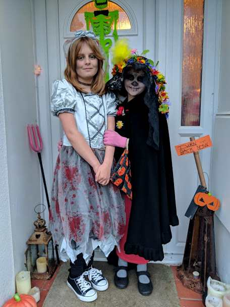 Image of two girls in fancy dress Halloween costume outside a decorated front door